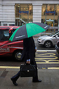 A businessman uses a large brolley during damp, gloomy weather in central London.