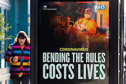 © Licensed to London News Pictures. 22/01/2021. London, UK. A woman without a protective face covering walks past the government's 'Bending the rules costs lives' publicity campaign poster in north London. The Office for National Statistics (ONS) has released figures which show the percentage of people testing positive for the virus decreased slightly in the week ending 16 January. During that period, an estimated one in 30 people had Covid-19 in London. Photo credit: Dinendra Haria/LNP
