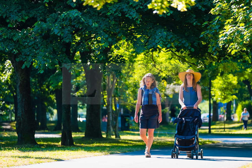 © Licensed to London News Pictures<br /> <br /> 26 June 2018 . Aberystwyth Wales UK<br /> <br /> UK Weather:  Two women  walking in the park in Aberystwyth at the start of yet another  day of hot unbroken sunshine.<br /> The UK is heading  into a mini heatwave, with temperatures forecast to hit 29º or 30º Celsius by the middle of the week<br /> <br /> photo creditKeith Morris / LNP