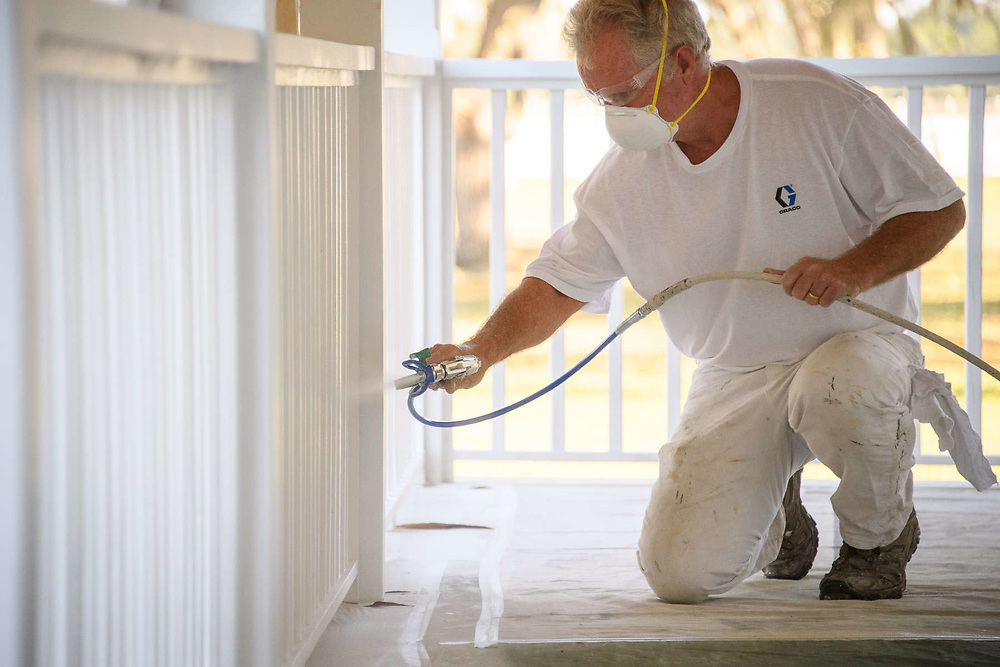 Painter using a Graco Airless Paint Sprayer on a wood deck of a residence.