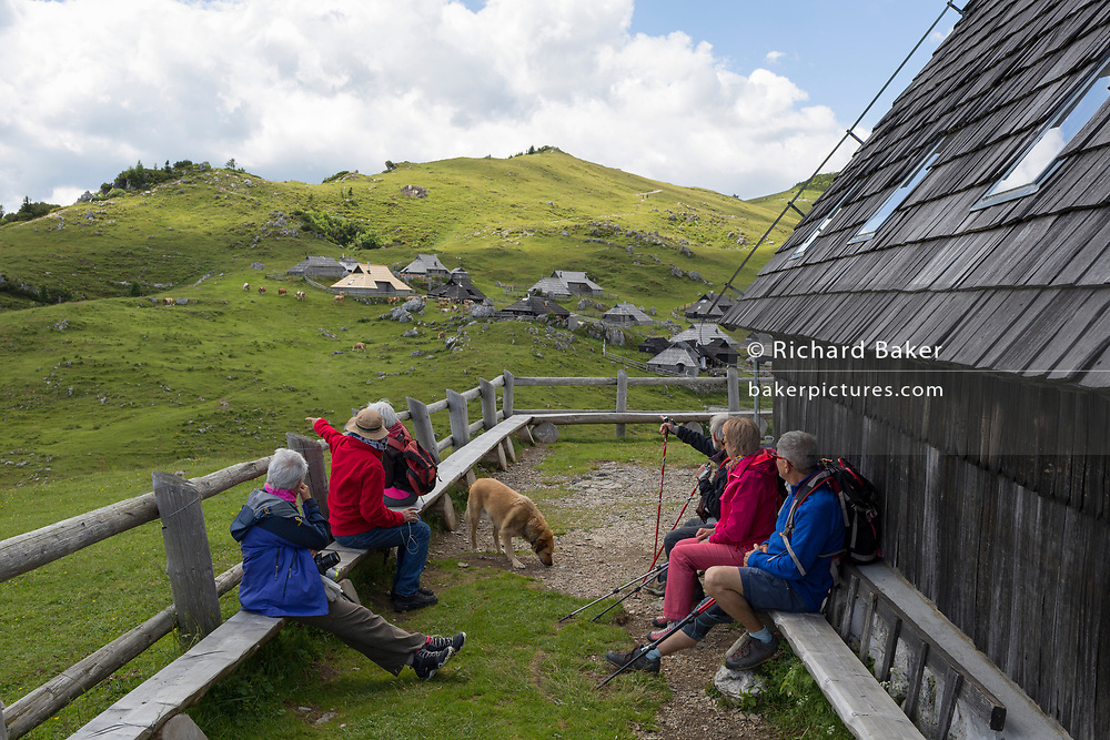 Walkers enjoy lunch at the chapel dedicated to Our Lady of the Snows, built in 1938 by the Slovenian architect Jože Plečnik, above the collection of Slovenian herders' mountain huts in Velika Planina, on 26th June 2018, in Velika Planina, near Kamnik, Slovenia. Velika Planina is a mountain plateau in the Kamnik–Savinja Alps - a 5.8 square kilometres area 1,500 metres (4,900 feet) above sea level. Otherwise known as The Big Pasture Plateau, Velika Planina is a winter skiing destination and hiking route in summer. The herders' huts became popular in the early 1930s as holiday cabins (known as bajtarstvo) but these were were destroyed by the Germans during WW2 and rebuilt right afterwards by Vlasto Kopac in the summer of 1945.