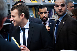 © Licensed to London News Pictures. FILE PICTURE 24/03/2017 Salon du Livre, Porte de Versailles, Paris, France. Alexandre Benalla (centre) pictured with Emmanuel Macron at the Paris Book Fair during the election campaign. Mr Benalla, a close security aide to Mr Macron, is facing disciplinary action after damning video evidence emerged of him assaulting demonstrators at a May Day demonstration while wearing a CRS riot helmet and a police armband - an ever present shadow to Mr Macron, Benalla continued to serve in his capacity as a security advisor and bodyguard following a light reprimand from the Elysee while the mounting scandal and accusations of an attempted cover up escalated. Macron called an emergency meeting on Sunday to manage the crisis, while Benalla was arrested and remanded in custody over the weekend on charges of violence by a public official, impersonating a police officer and the illegal use of police insignia. Benalla was due to be getting married on Saturday. Macron's popularity ratings fell to an all time low of 39% last week, quashing hopes that the World Cup win would give him a boost.  Photo credit: Guilhem Baker/LNP