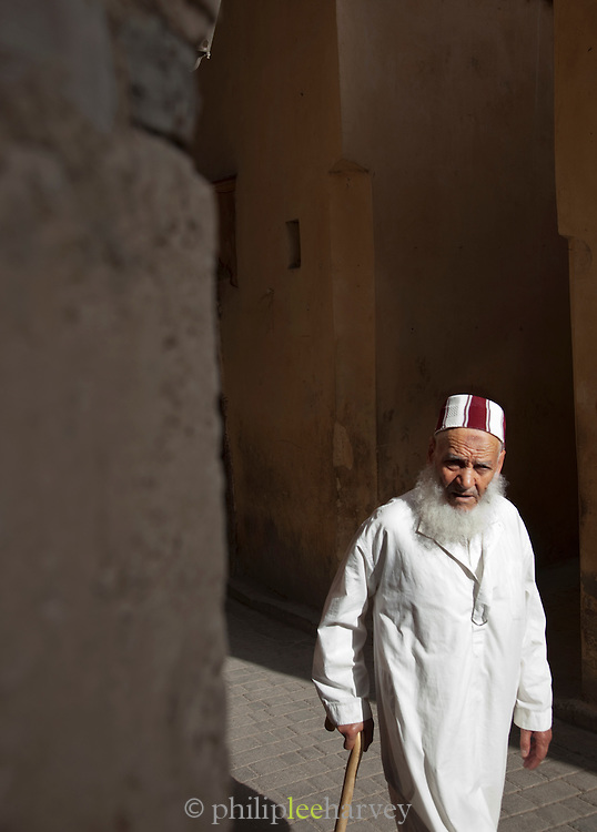 An old man walking in the narrow streets of the medina in Fes, Morocco