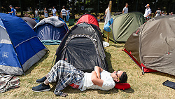 © Licensed to London News Pictures. 06/07/2018. LONDON, UK. A spectator sunbathes whilst queuing for day tickets in Wimbledon Park to the Wimbledon Tennis Championships.  Temperatures forecast to approach 30C mean that the majority have taken precautions to protect themselves from the sun by wearing sunglasses and sunhats.  Photo credit: Stephen Chung/LNP