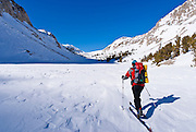 Backcountry skier crossing Loch Leven under Piute Pass, John Muir Wilderness, Sierra Nevada Mountains, California USA