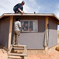 032713     Brian Leddy<br /> Dough Vilsack, Keyvan Izadi and Rachel Jones install a small solar panel on the roof of Alice Dougi's home near Bodaway Gap Wednesday, March 27.