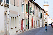 Domaine d'Aupilhac. Montpeyroux. Languedoc. France. Europe. The village street in front of the winery. A sign on the wall. A person walking on the street.