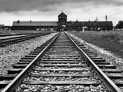 Monochrome photo of the rail tracks and entrance gate to the Auschwitz-Birkenau concentration camp, Auschwitz, Poland
