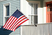 Patriotic Stars and Stripes flag at traditional clapboard home with front stoop in Newport, Rhode Island, USA