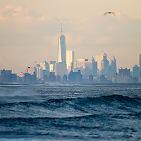 Several days of persistent easterly winds cause big waves to crash along the surf at Sandy Hook NJ.   Waves to 10 feet with big white water, current and foam pounded the area that was just replenished with sand. In the background is New York City with One World Trade Center dominating the skyline.