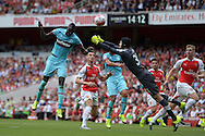 Cheikhou Kouyate of West Ham United heads the ball past Goalkeeper Petr Cech of Arsenal to score his sides first goal of the game to make it 0-1. Barclays Premier League, Arsenal v West Ham Utd at the Emirates Stadium in London on Sunday 9th August 2015.<br /> pic by John Patrick Fletcher, Andrew Orchard sports photography.