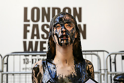 "© Licensed to London News Pictures. 13/09/2019. London, UK. A campaigner from People for the Ethical Treatment of Animals (PETA) protests against the hazardous waste associated with the leather industry is covered in black ""toxic slime"" on the opening day of London Fashion Week. Photo credit: Dinendra Haria/LNP"