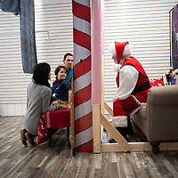 QUAKERTOWN, PA:  Vincent Rivas, 5, reacts while looking through plexiglass at Roy Warburg, 65, who portrays Santa Claus at the Quakertown Farmer's Market in Quakertown, PA on December 5, 2020. Warburg was a maintenance man at the 88 year old shopping destination for 15 years before staring to depict Santa Claus 5 years ago.  The pandemic has forced difficult decisions about maintaining the holiday tradition of visits to Santa Claus versus safety concerns.  Plexiglass dividers, face shields, and physical distancing are among the precautions for those locations that have proceeded with Santa photo opportunities.  CREDIT:  Mark Makela for The New York Times