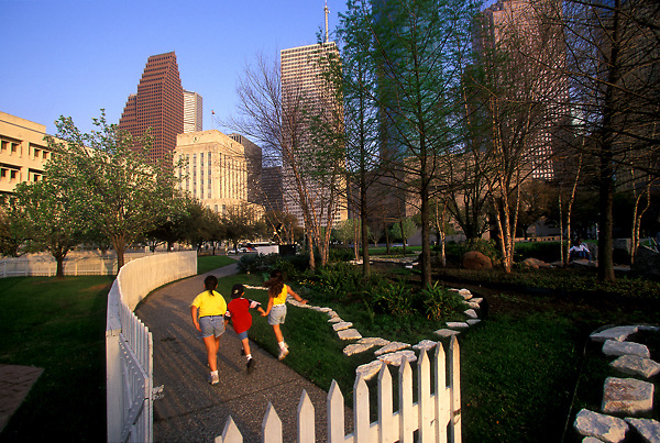 Stock photo of three girls skipping and holding hands in a park in downtown Houston, Texas.