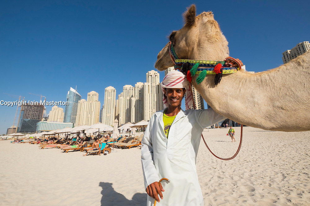Tourist camel and owner on beach at JBR Jumeirah Beach Residences in Marina district of Dubai United Arab Emirates