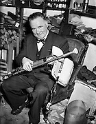 """Leo Rowsome making pipes at 9 Belton Park Road.16/06/56..Leo Rowsome (05/04/1903 - 20/09/1970) was the third generation of an unbroken line of uilleann pipers. He was performer, manufacturer and teacher of the uilleann pipes - the complete master of his instrument. He devoted his entire life to the uilleann pipes..Samuel Rowsome, Leo's grandfather sent his sons, John, Thomas and William to a German teacher of music who resided in Ferns, near their home in Co. Wexford to learn the theory of music and how to play various instruments. This knowledge was passed on through William to his son, Leo who made good use of it in his teaching, writing music for his many pupils..Leo was born in Harold's Cross, Dublin in 1903. His father, William realised that his son had the ability to become a talented musician and craftsman. Constantly watching his father making and repairing instruments, Leo learned the art of pipe making and instrument repair. So rapid was his progress at piping that in 1919 at the age of sixteen he was appointed teacher of the uilleann pipes at Dublin's Municipal School of Music (now D.I.T. Conservatory of Music & Drama) for 50 years. He also taught at Dublin's Pipers Club of which he was President..In 1925, Leo's father died at the age of fifty-five. Leo successfully carried on the family business, after completing his own set of pipes in 1926. The instrument remained an object of fascination and veneration for countless audiences at home and abroad..Leo was the first uilleann piper to perform on Irish National Radio in the early 1920s when he played solo and later in duets with Frank O'Higgins (fiddle), Micheal O Duinn (fiddle) and Leo's brother John (fiddle). Leo's """"All Ireland Trio"""" comprised Neilus Cronin, flute, Seamus O'Mahony, fiddle and Leo pipes. He formed his Pipes Quartet in the mid 1930s and broadcast regularly throughout the 1940s/50s. Leo was the first Irish artist to perform on BBC T.V. (1933). He made many recordings for Decca, Columbia and"""