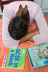 Girl sitting at kitchen table with head in arms; studying for school exams,