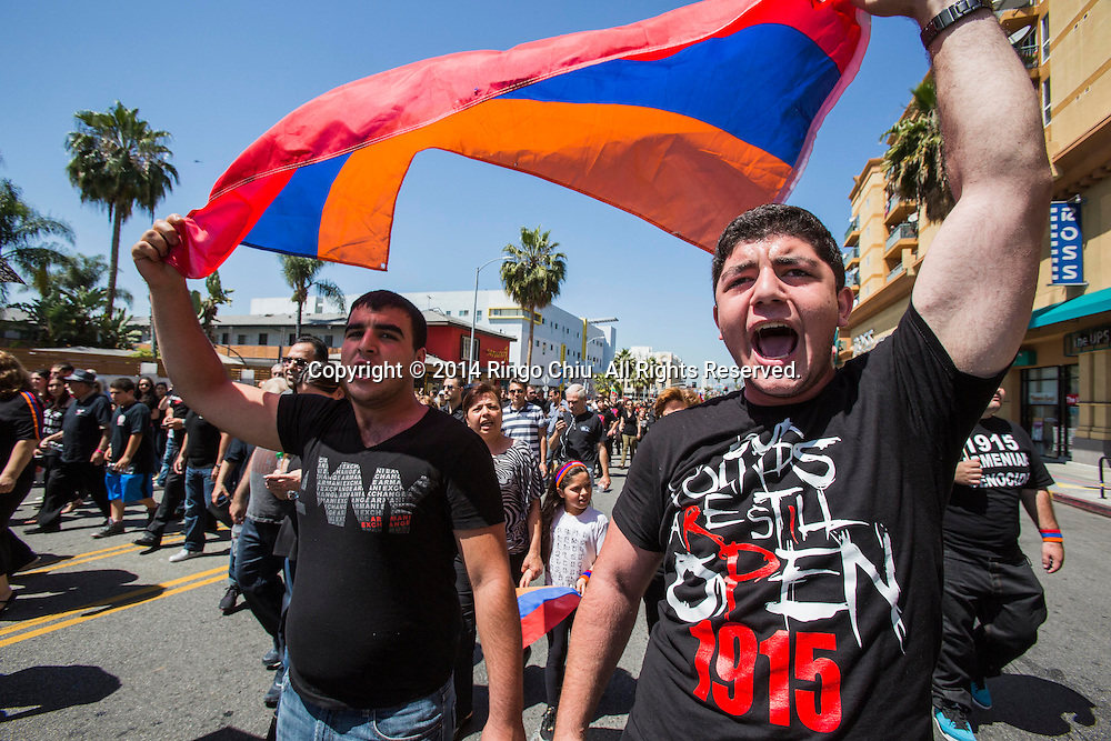 Aram Vardanyan, right, and Hovo Demirchyam, left, carry an Armenia flag as thousands of Armenians march along Hollywood Boulevard to mark the 99th anniversary of the beginning of the Armenian genocide and to call on the Turkish government to recognize the deaths of about 1.5 million people, in Los Angeles on Thursday, April 24, 2014. (Photo by Ringo Chiu/PHOTOFORMULA.com)