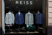 Reiss shop suits on display in a central London window. Four jackets with shirts and tie suggestions have been lined alongside each other to take up the width of this sunlit window. The brand name Reiss is seen above the hangers. David Reiss started his brand in 1971, establishing a design philosophy centred on creating directional, design-led menswear, womenswear and accessories.