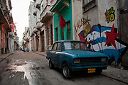 A Lada car in the street in Havana Centro central Havana, with colourful murals paintings behind it.