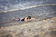 Man lies on beach and have sunbathe, he lets his legs sinking in water, Nam Dinh province, Vietnam, Asia.