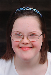 Portrait of teenage girl with Downs Syndrome wearing hairband smiling,