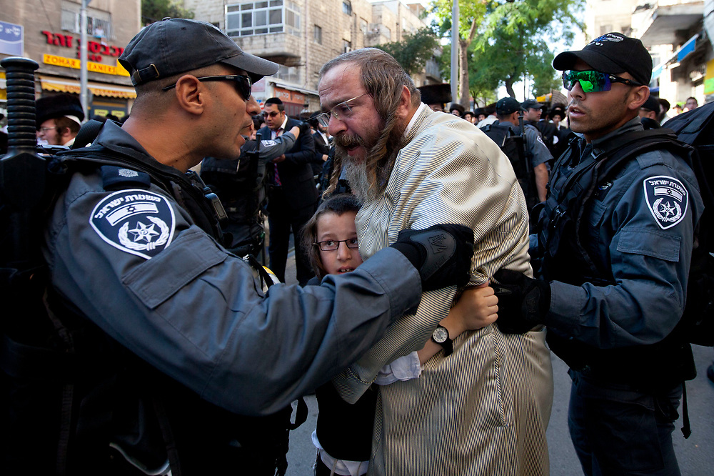 Israeli policemen scuffle with ultra-Orthodox protesters as they attempt to block Neviim Street, a central thoroughfare in Jerusalem on July 16, 2011. Close to a thousand ultra-Orthodox Jewish men held a demonstration against the desecration of Shabbat, marking one hundred weekends to the opening of the Karta municipal parking lot in the capital.