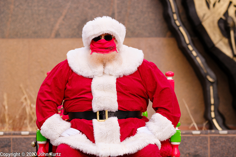 """29 NOVEMBER 2020 - DES MOINES, IOWA: A mask wearing, socially distanced Santa Claus waits for children to visit during the holiday """"Promenade"""" in the East Village neighborhood of Des Moines. This is the 19th year of the Promenade, a Des Moines tradition that draws shoppers and holiday revelers into the East Village neighborhood. This year's promenade is designed with CDC coronavirus guidelines in place, including social distancing and mask wearing.      PHOTO BY JACK KURTZ"""