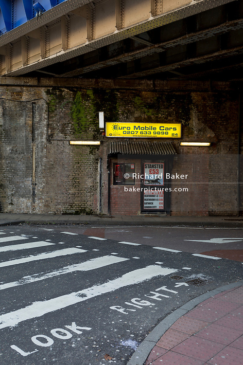 A taxi cab office advertising airport run fairs beneath a Victorian bridge near Waterloo station, on 30th January 2018, in the south London borough of Southwark, England.