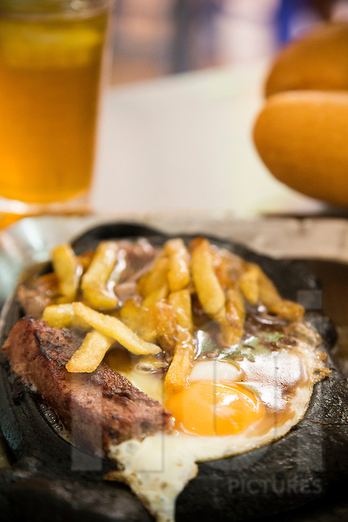 Traditional vietnamese dish bo bit tet, a beefsteak smothered in gravy with french fries, egg and pork terrine. Hoe Nhai street, Hanoi, Vietnam, Southeast Asia