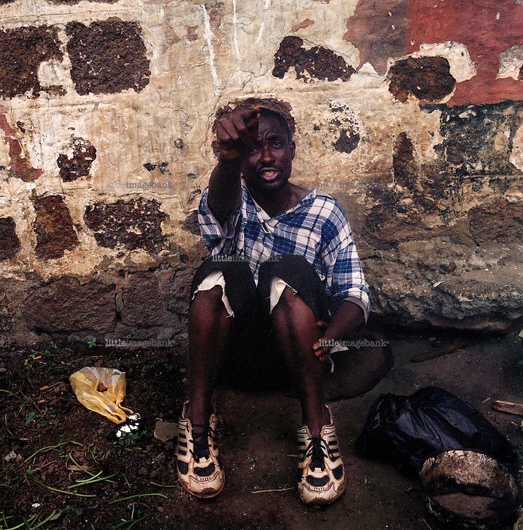 A man sits outside in a courtyard in  Kissy mental institution. According to the United Nations Development Programme (UNDP), Sierra Leone is one of the poorest nations on the face of earth. Recently it saw the end of a decade of civil-war, that caused an extreme suffering for the population. Tens of thousands became victims of armed forces on amphetamine, that cut limbs for fun, child soldiers armed to the teeth with Kalashnikows.  An entire population was driven away from their homes and the infrastructure was completely destroyed. Today thanks to some 15.000 soldiers from the UN-AMSIL peacekeeping force, order is restored and dailylife is again more or less as it once was. Many of those who saw the horrors of the war can manage to move on with their lives, many cant manage. <br /> Kissy Mental Hospital is located on a small hilltop on the north part of the capitol Freetown in a small suburbia named Kissy, The hospital compound was constructed in the mid 1800s under the bristish colonny empire. It has served several different purposes in the past, today it serves as the only institution for individuals suffering from mental illness in the whole country. <br /> The chief nurse tells that few turns back to narmality, some of the young boys are examples of success. He admits that its not the easiest place to become sane, rather a place that makes you insane.