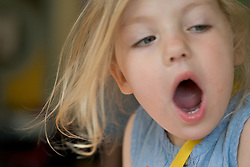 Portrait of a young girl yawning,