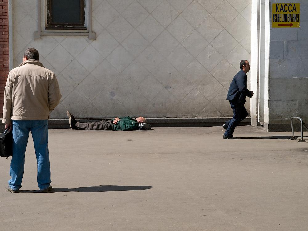 Schlafender Mann an der Rückseite des Kasaner Bahnhofs (Kasanski woksal) welcher einer der acht Fernbahnhöfe in Moskau ist. Er liegt am Komsomolskaja-Platz, in unmittelbarer Nähe zum Jaroslawler und dem Leningrader Bahnhof, und ist bis heute einer der größten Bahnhöfe der russischen Hauptstadt.<br /> <br /> Sleeping person on the backside of the Kazansky Rail Terminal (Kazansky vokzal) which is one of nine rail terminals in Moscow, situated on the Komsomolskaya Square, across the square from the Leningradsky and Yaroslavsky terminals.