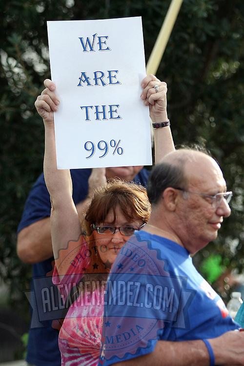 A woman pickets during a parade at the start of the Republican National Convention in Tampa, Fla. on Wednesday, August 29, 2012. (AP Photo/Alex Menendez)