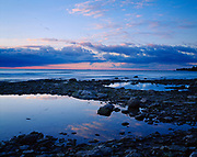 Pastel light of sunrise reflected in rock-lined pond along the shore of Lake Erie, Kelleys Island, Ohio.
