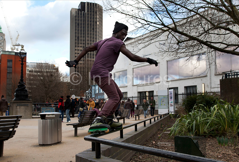 """A walk along the River Thames on the Southbank in London. Aggressive inline skater performs a glide trick. Aggressive inline is a form of inline skating executed on specially designed inline skates with focus on grinding and spins. Participants refer to the activity as rollerblading, """"blading"""", """"skating"""" or """"rolling"""". Aggressive skating tricks can be performed on street obstacles or on ramps. Street skaters perform more grinds and slides, whereas ramp skaters have more air-time and therefore can perform other, often acrobatic tricks. This area is very popular especially on the weekends for Londoners to walk and see different arts, culture and entertainment."""
