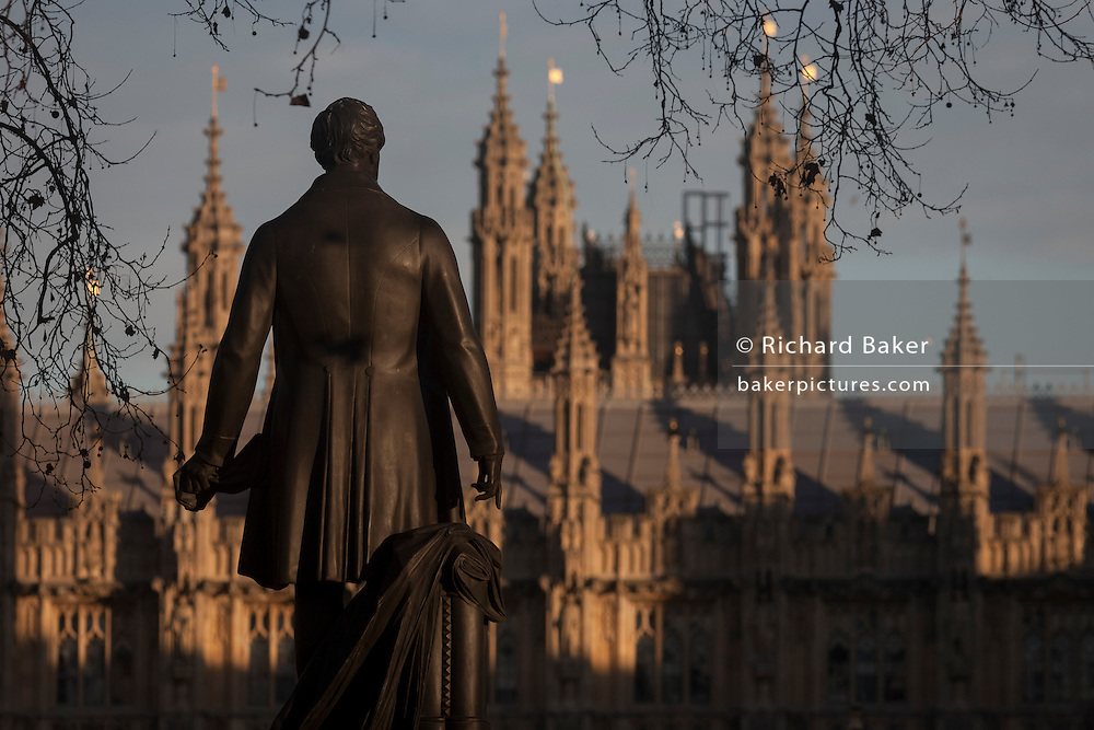 """The statue of Sir Robert Peel and the British Houses of Parliament, on 17th January 2017, in Parliament Square, London England. The Elizabeth Tower (previously called the Clock Tower) named in tribute to Queen Elizabeth II in her Diamond Jubilee year – was raised as a part of Charles Barry's design for a new palace, after the old Palace of Westminster was largely destroyed by fire on the night of 16 October 1834. The new Parliament was built in a Neo-gothic style, completed in 1858 and is one of the most prominent symbols of both London and England. Sir Robert Peel, was a British statesman and member of the Conservative Party, served twice as Prime Minister of the United Kingdom and twice as Home Secretary. He created the modern police force and officers known as """"bobbies"""" and """"peelers"""""""