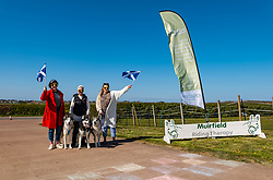 East Lothian, Scotland, United Kingdom, 25th April 2021. Virtual Kilt Walk: Kilt walkers supporting Muirfield Riding Therapy charity cross a 'finish line' to celebrate their participation in their 'Round the World'  fund raising campaign. Each team chose a destination and walked, cycled or rode the miles from home to their chosen point, totalling the 24,900 miles of the earth's circumference and raising over £10,000. Pictured: The BaxterStorey team who covered the distance to Alaska, with Siberian huskies. Sally Anderson / EdinburghElitemedia.co.uk