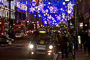 Hailing a black taxi cab among Christmas decorations and traffic in Regent Street, London, United Kingdom