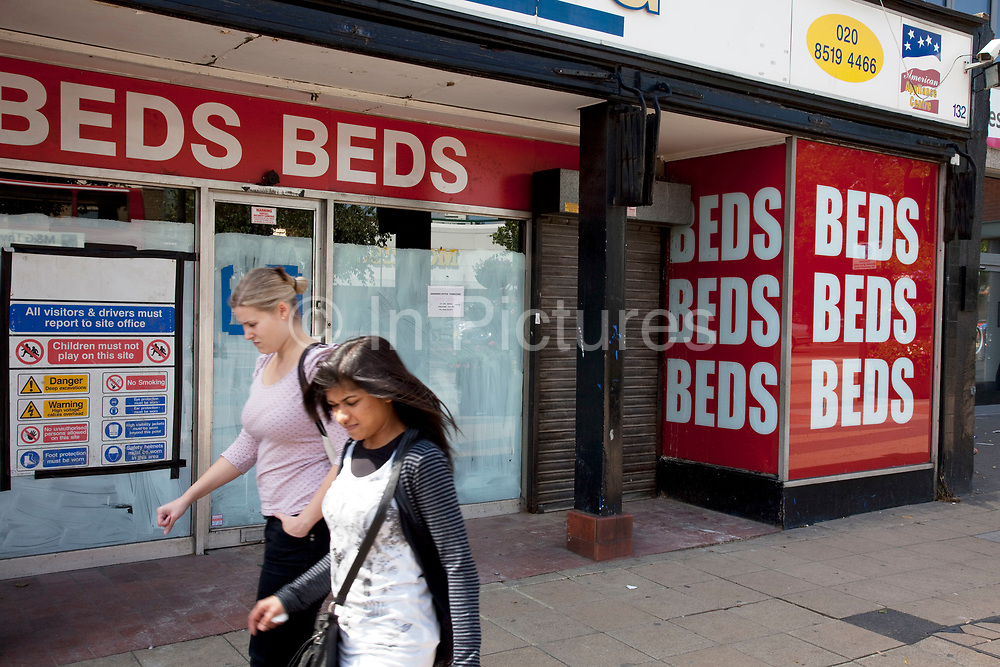People pass a closed down and boarded up shop in Stratford in East London. This is a relatively poor area of London, but in recent years has seen much regeneration, the construction of a major transport hub and various shopping complexes. Stratford is adjacent to the London Olympic Park and is currently experiencing regeneration and expansion linked to the 2012 Summer Olympics. (Photo by Mike Kemp/For The Washington Post)