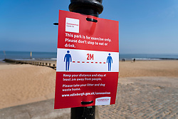 Portobello, Scotland, UK. 25 April 2020. Views of people outdoors on Saturday afternoon on the beach and promenade at Portobello, Edinburgh. Good weather has brought more people outdoors walking and cycling. Police are patrolling in vehicles but not stopping because most people seem to be observing social distancing. Warning sign about social distancing.   Iain Masterton/Alamy Live News