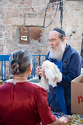 The Butchers chicken stall, Mea Shearim, Jerusalem, Israel<br /> Kaparot, an aged old Jewish tradition were a chicken is waved over the believer's head, reliving the person from all sins which are passed on to the chicken. The chicken is slaughtered and at times given to charity. Photographed in Mea Sharim, Jerusalem