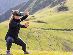 Woman practicing Tai Chi moves with virtual reality glasses on mountain