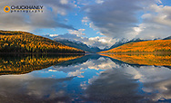 Mountain peaks reflect into Bowman Lake in autumn in  Glacier National Park, Montana, USA