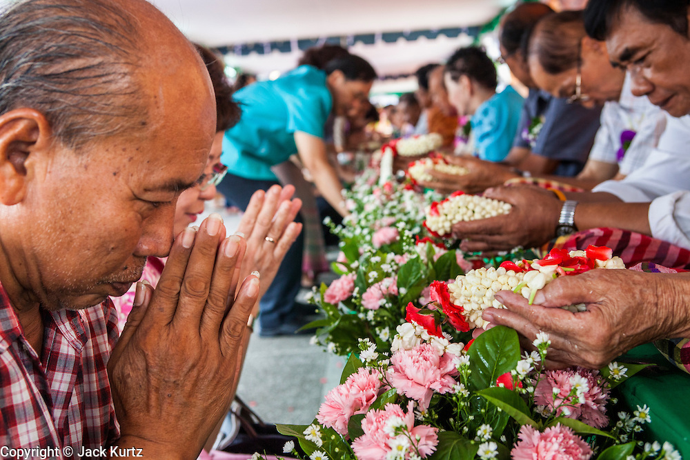 13 APRIL 2013 - BANGKOK, THAILAND: A man prays after he made merit by washing the hands of an elderly woman in scented water during a Songkran observance at Bangkok City Hall. The Songkran tradition of throwing water on people started with the traditional hand washing. Songkran is the traditional Thai New Year's Festival. It is held April 13-16. Many Thais mark the holiday by going to temples and making merit by giving extra alms to monks or offering extra prayers. They also mark Songkran with joyous water fights. Songkran has been a national holiday since 1940, when Thailand moved the first day of the year to January 1.    PHOTO BY JACK KURTZ