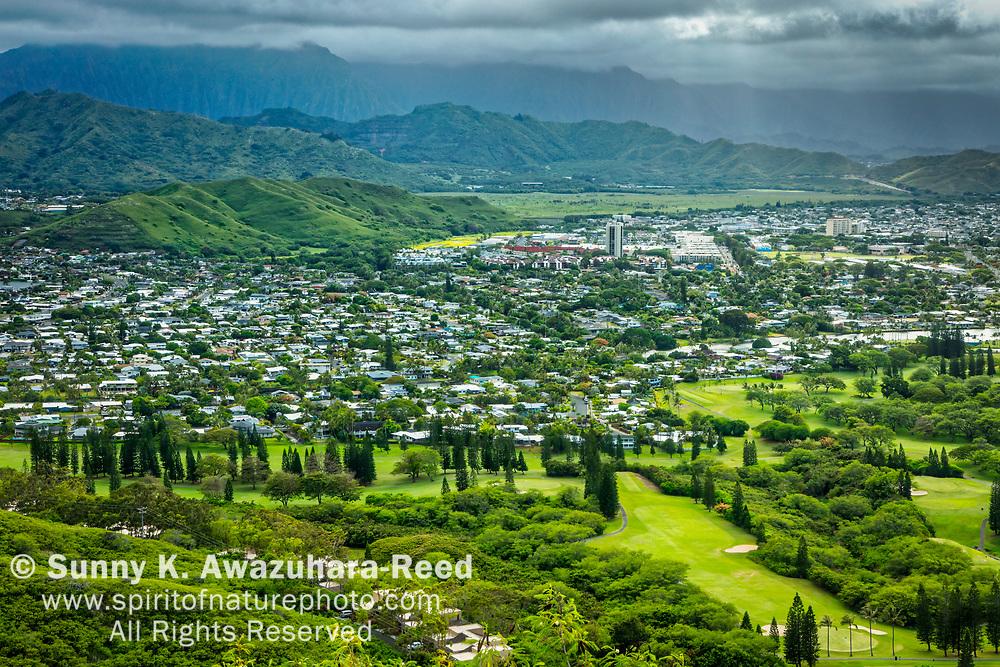 Sun beaming through the clouds over Koʻolau Range and Kailua residential neighborhood, viewed from Lanikai Pillbox Trail, Kailua, Island of Oahu, Hawaii.