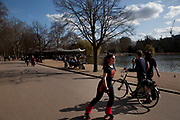 People gather to walk along the edge of The Serpentine in Hyde Park, London. This is a popular place for rollerblading and other activities.
