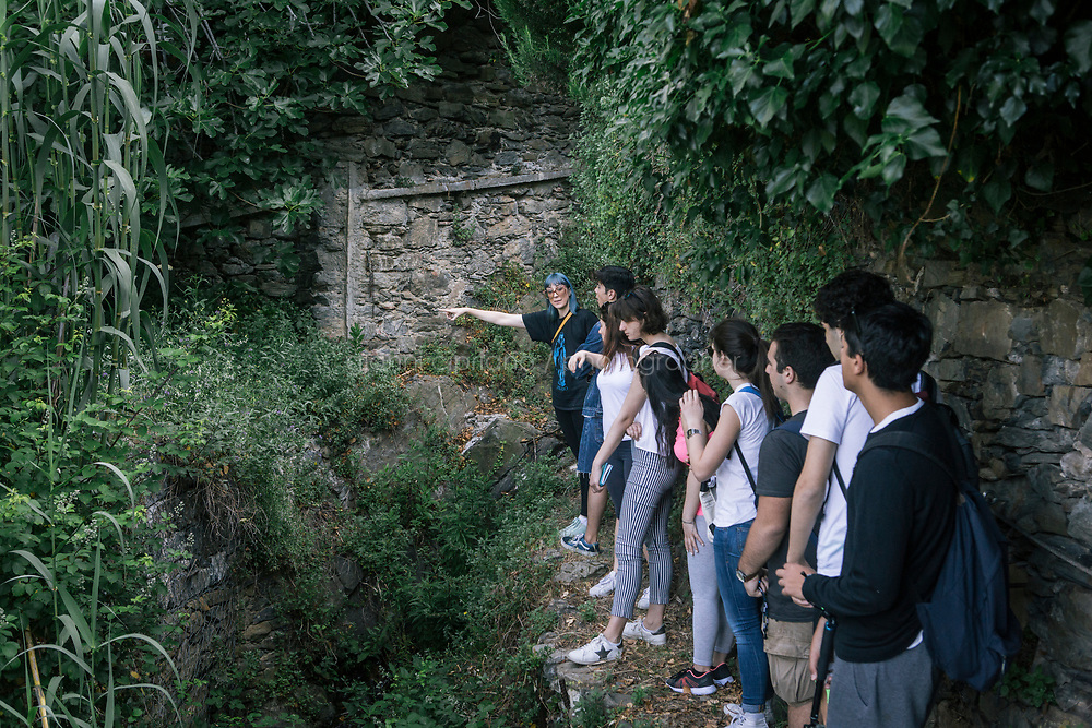 VERNAZZA, ITALY - 1 JUNE 2017: A high-school class is here during a field trip with Margherita Ermirio, part of a UNESCO Youth program to enhance the relationship between the young and their territory, here in Vernazza, Italy, on June 1st 2017. This class has been studying terracing in the Cinque Terre from an historical point of view, comparing the 18th century maps with Google earth's most recent pictures. From the measures taken during the field trip, students will make a 3D design of the area.<br /> <br /> Given its jagged coastline and manifold mountainous chains, Italy is believed to hold a record in Europe with an estimated 300,000 hectares of terracing, and 170,000 kilometers of dry stone walls— 20 times the length of the Great Wall of China.<br /> Liguria, the narrow half-moon shaped region along the northern<br /> Thyrrenian sea, has the highest concentration, and terracing is in<br /> poor shape there. In Vernazza, almost half of the terracing is in<br /> ruins.<br /> <br /> Terraced vineyards, apple and lemon groves horizontally run around the green slopes of the Cinque Terre. The stone walls have allowed such vital cultivation in the area and prevented land slides. Since the 1960s, the ancient walls have been largely<br /> abandoned, posing hydro-geological threats to the same villages during<br /> heavy rains and, in general, as time passes.<br /> <br /> Since the 2012 flood - when tons of mud invaded the<br /> village's main road, shops and and homes, isolating the area and<br /> taking three lives - Margherita Ermirio has agreed with the various land lords to take<br /> over 6,000 square meters of land parcels that needed to be cleaned up,<br /> in order to fix them and thus prevent land slides, but also to show to<br /> the younger generations that agriculture is still possible in the<br /> Cinque Terre.