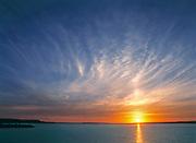 Cirrus clouds take on the colors of the sun setting over Lake Sakakawea, in North Dakota.