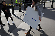 While a couple do a selfie in spring snshine, a woman walks past carrying a white board with blue arrows pointing the correct direction, on 21st March 2017, in Trafalgar Square, London, England.